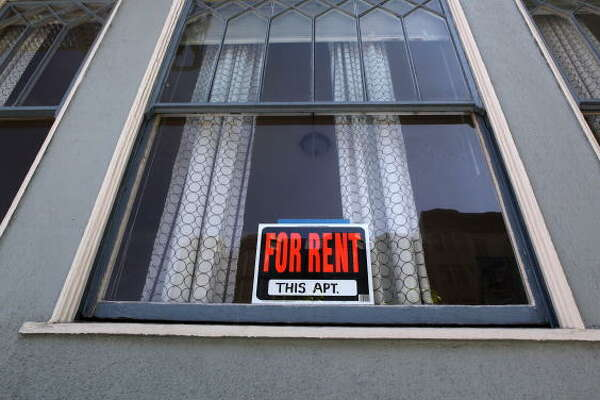 A sign advertising an apartment for rent is displayed in a window. Those in the apartment industry say that demand is dropping across the city.