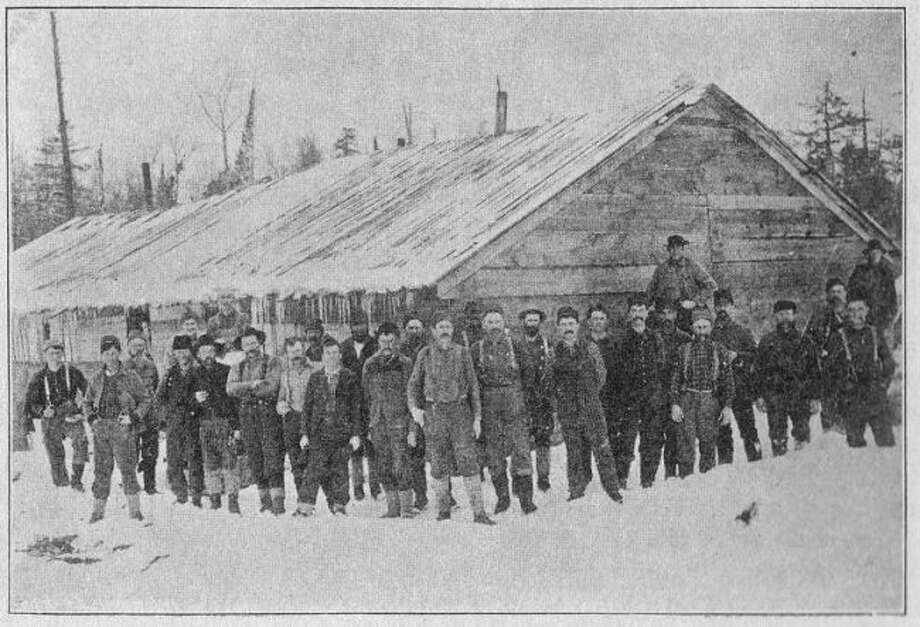This hearty group of lumberjacks pose in front of their logging camp in this photograph from the 1880s.