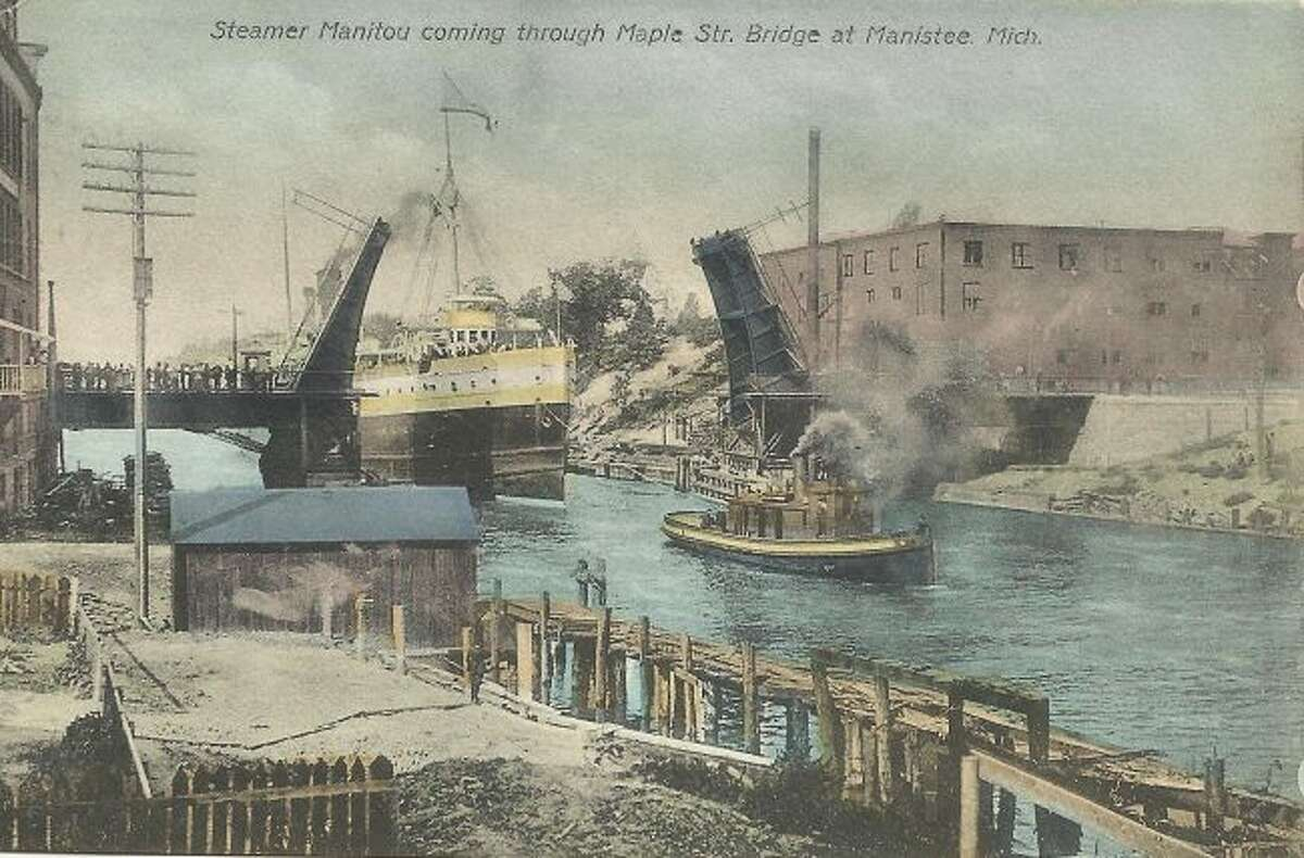A popular scene past and present in Manistee is a ship coming into the port of Manistee. Here the steamer Manitou is pulled in by a tug boat though the Maple Street Bridge.