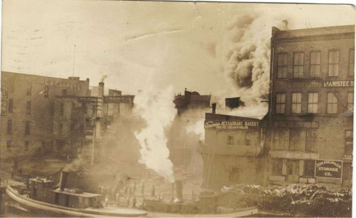 A large fire roars through a building in downtown Manistee in this early 1900 photograph.