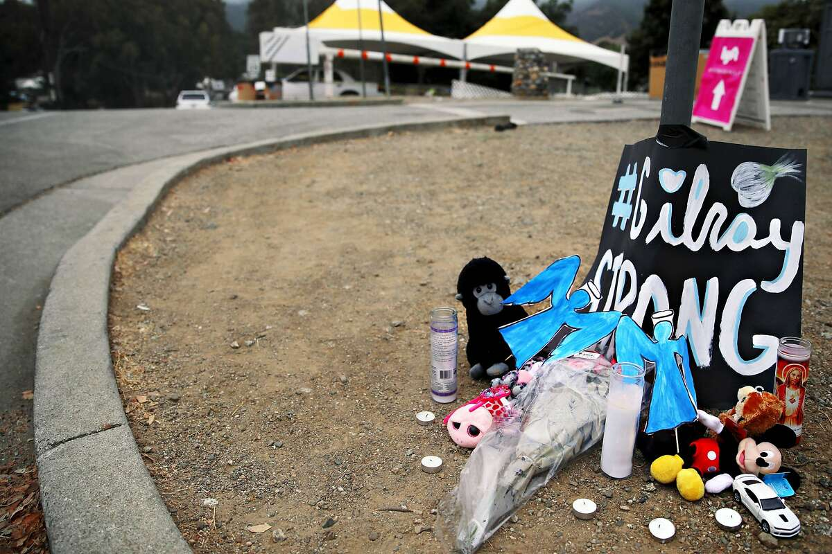 A memorial with stuffed animals, candles, a toy car and a poster stating