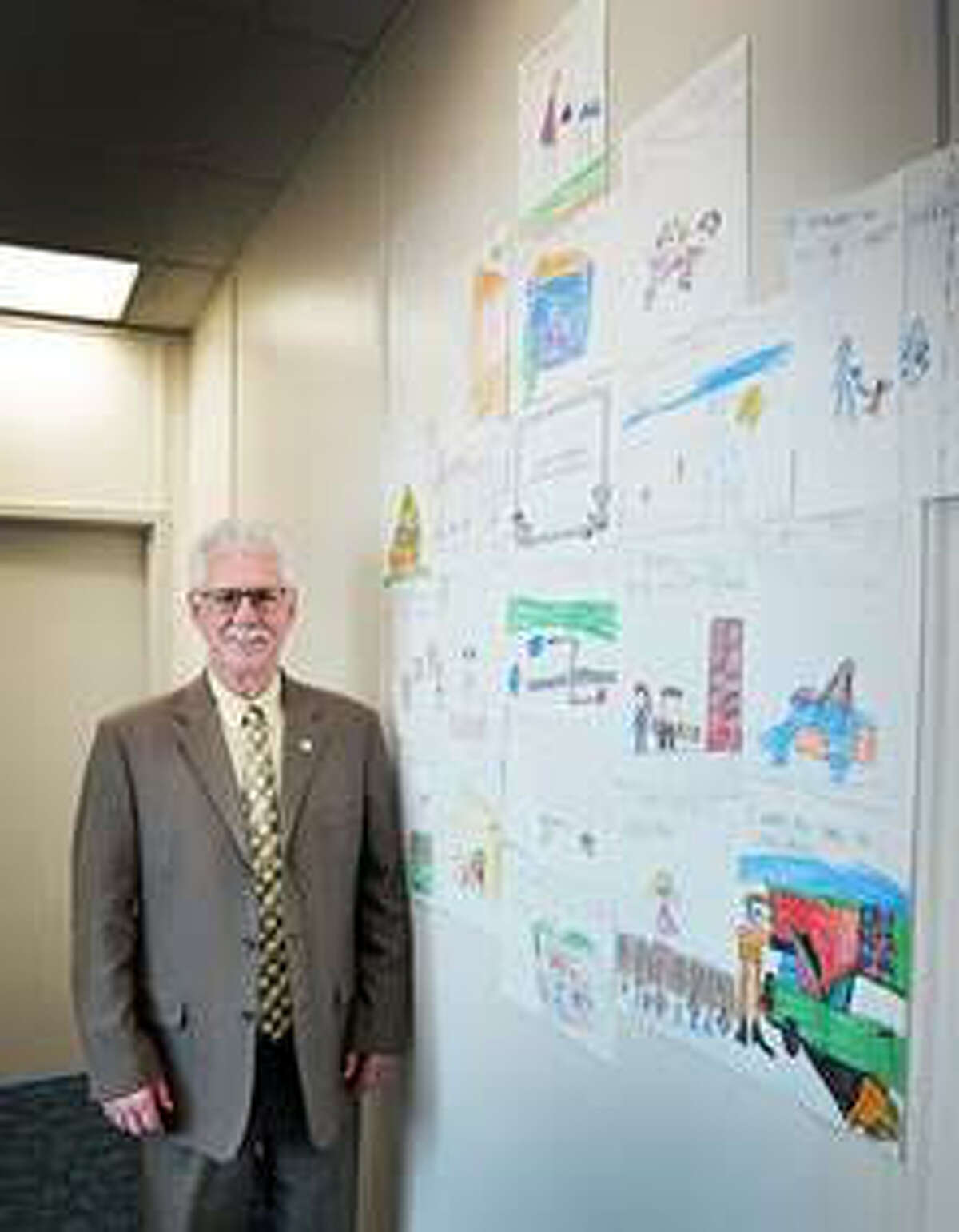 """Sen. Darwin Booher poses in his office alongside artwork from Kaleva Norman Dickson students artwork that was created by Lisa Gutowski's kindergarten class. The artwork was part of the """"Through the Eyes of Child"""" program that runs until the end of the year."""