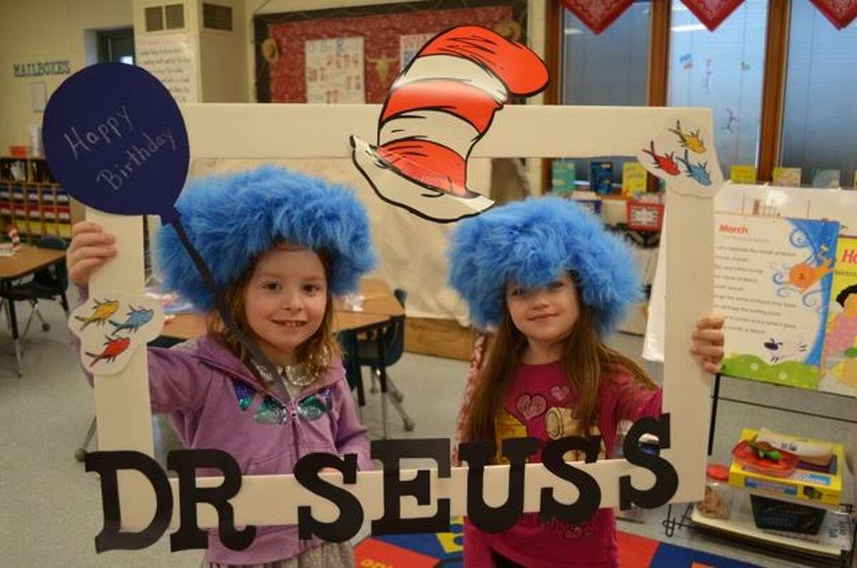 Bear Lake students Kamryn Crawford and Chloe Emigh proudly show off the sign that adorned the Bear Lake School first grade classroom on the birthday of Dr. Seuss.