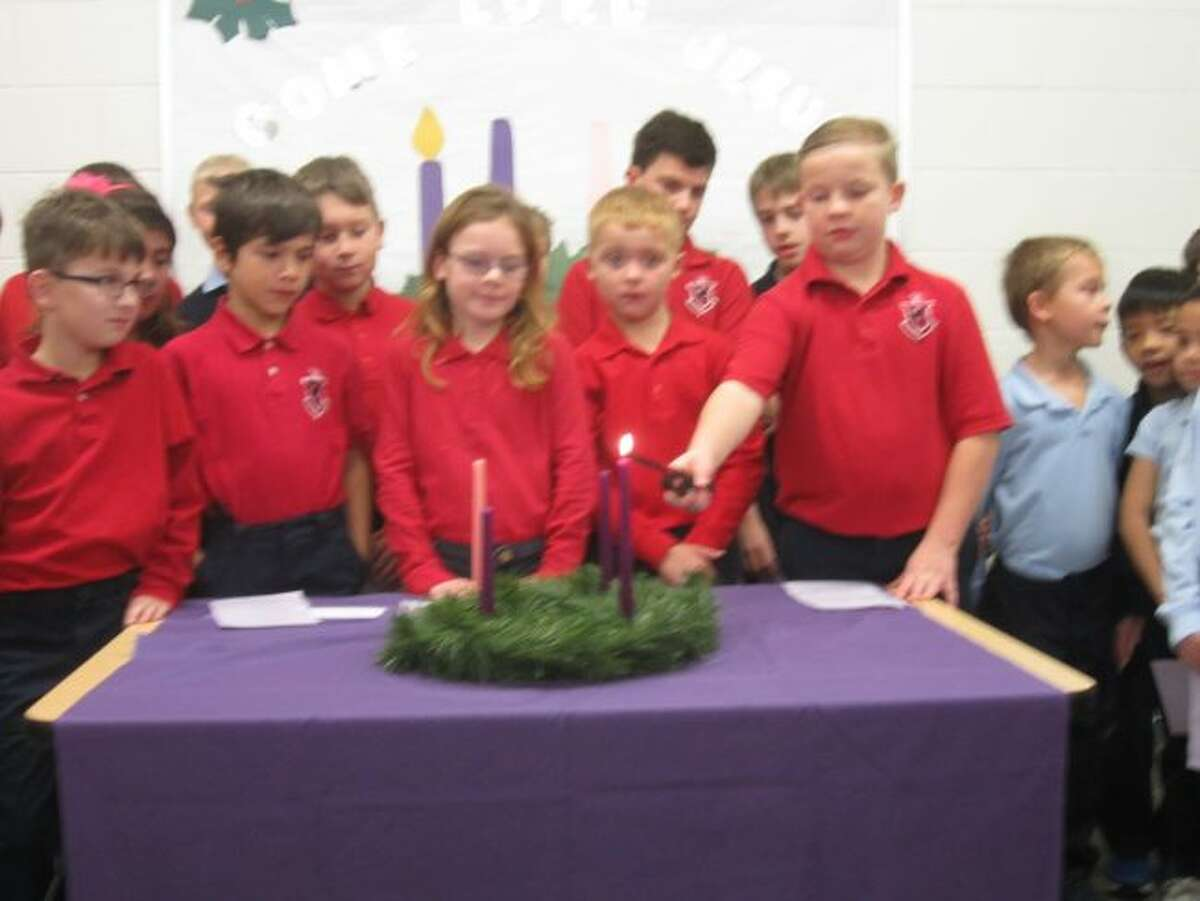 Lighting the first week's Advent candle is Manistee Catholic Central student Nathan Oleniczak.