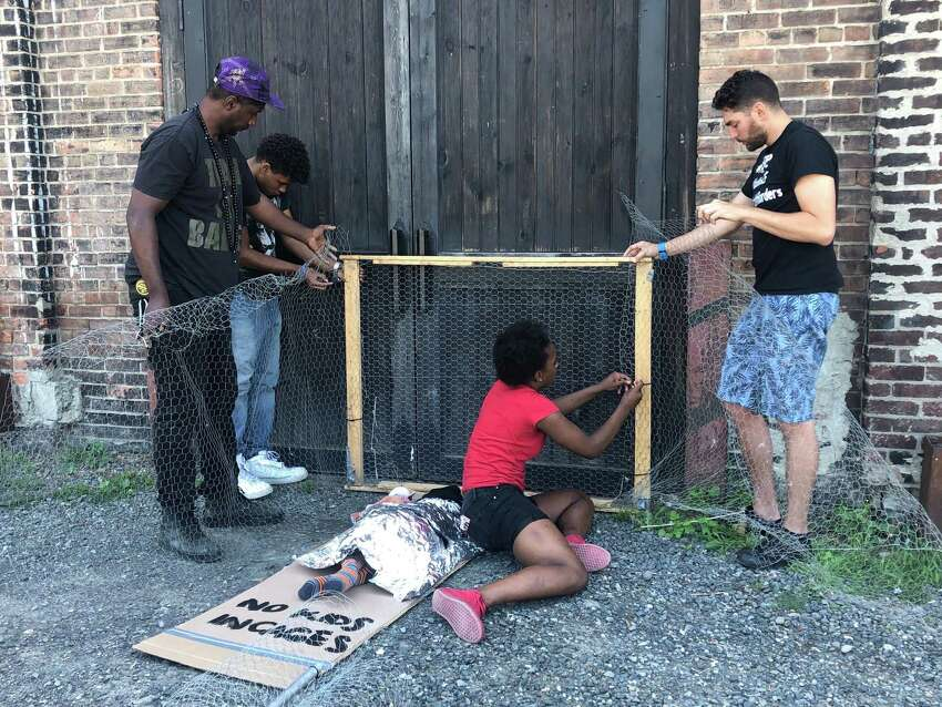 Bryan MacCormack, executive director of the Columbia County Sanctuary movement, helps staff members and teenage participants at the non-profit organization Kite's Nest build protest art to look like a migrant child in immigration detention in Hudson, N.Y. on July 24, 2019.
