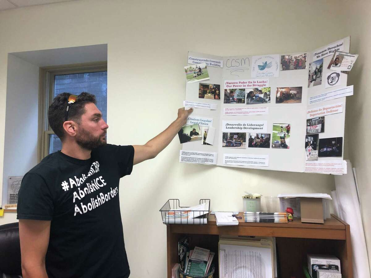 Bryan MacCormack, executive director of the Columbia County Sanctuary Movement, shows a poster sharing about the organization's work inside his office in Hudson, N.Y. on July 24, 2019. CCSM recently pushed the county to add a translation function to their website.