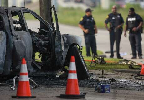 Houston Police officers investigate the scene where a driver careened off Interstate 45 and hit a light pole along the frontage road on July 15, 2019. The vehicle caught fire, as well as a motorcycle dealership near the crash.
