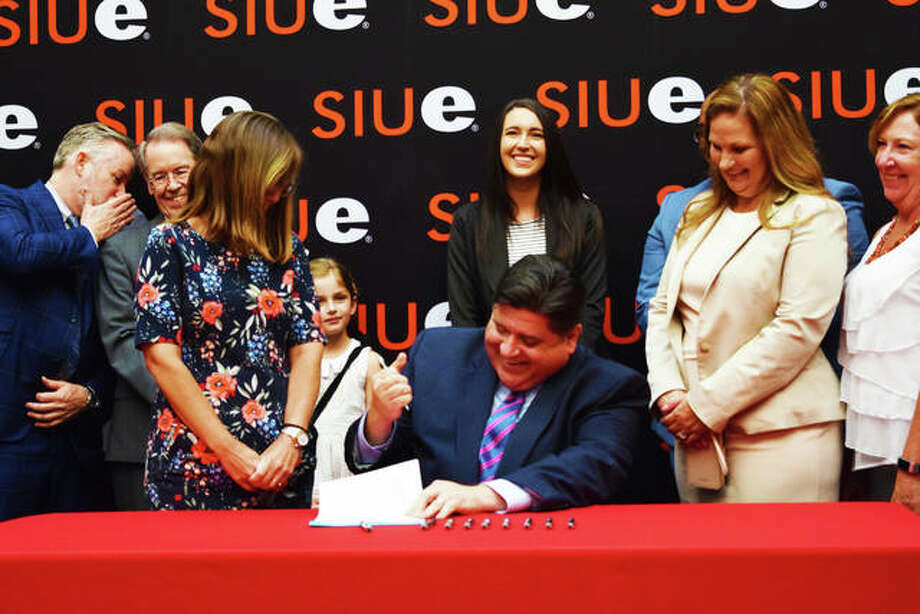 Gov. J.B. Pritzker (center) signs into action House Bill 2239 at SIU-Edwardsville campus with Rep. Katie Stuart (left) and Sen. Rachelle Crowe (right) at his sides. Photo: Tyler Pletsch | The Intelligencer