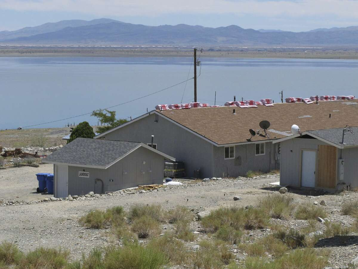 This photo taken Monday, July 29, 2019, shows a triplex with shingles stacked on top on Cliff House Road behind the sign for a nearby resort along the shore of Walker Lake about 10 miles north of Hawthorne, Nev., that authorities searched in connection with an investigation into the shooting the day before at a festival in Gilroy, Calif. Santino Legan was believed to have lived in the middle unit of the three-unit triplex before the shooting. (AP Photo/Scott Sonner)