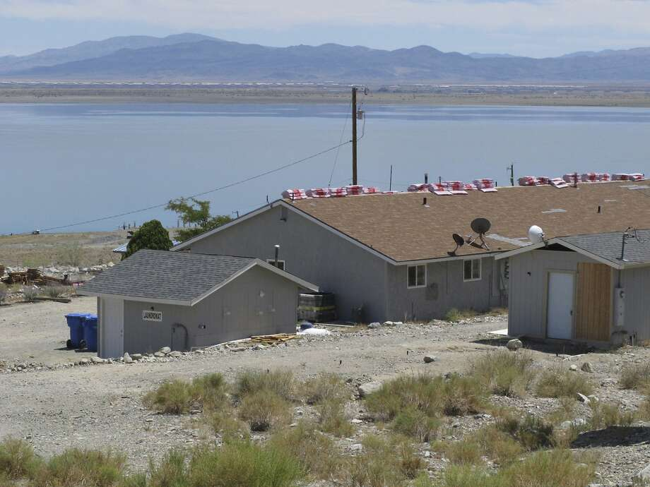 This photo taken Monday, July 29, 2019, shows a triplex with shingles stacked on top on Cliff House Road behind the sign for a nearby resort along the shore of Walker Lake about 10 miles north of Hawthorne, Nev., that authorities searched in connection with an investigation into the shooting the day before at a festival in Gilroy, Calif. Santino Legan was believed to have lived in the middle unit of the three-unit triplex before the shooting. (AP Photo/Scott Sonner) Photo: Scott Sonner, Associated Press