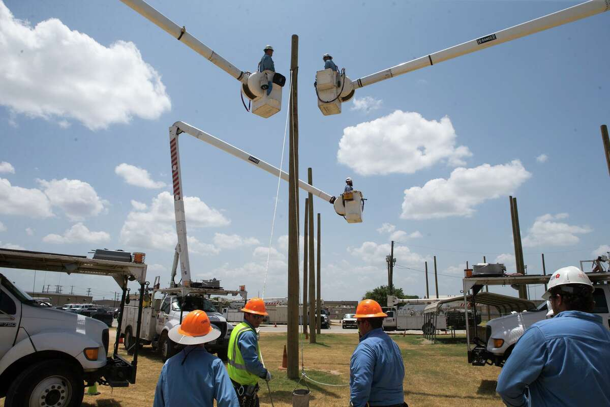 A simulation challenges eight interns to install an angle, July 30, 2019, at CPS Energy's training grounds in San Antonio. CPS energy employees instal off of bucket trucks while interns haul equipment up rope lines to them. Rebecca Slezak/Staff photographer