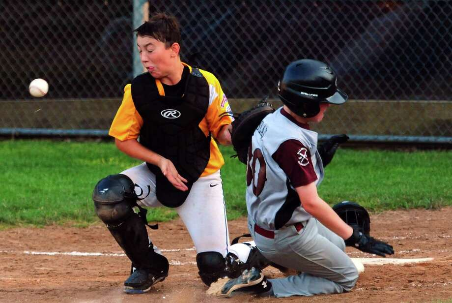 North Haven's John Slais slides into home plate as Madison catcher Paul Calandrelli misses the ball for the tag during little league baseball action in Willimantic, Conn., on Tuesday July 30, 2019. Photo: Christian Abraham / Hearst Connecticut Media / Connecticut Post
