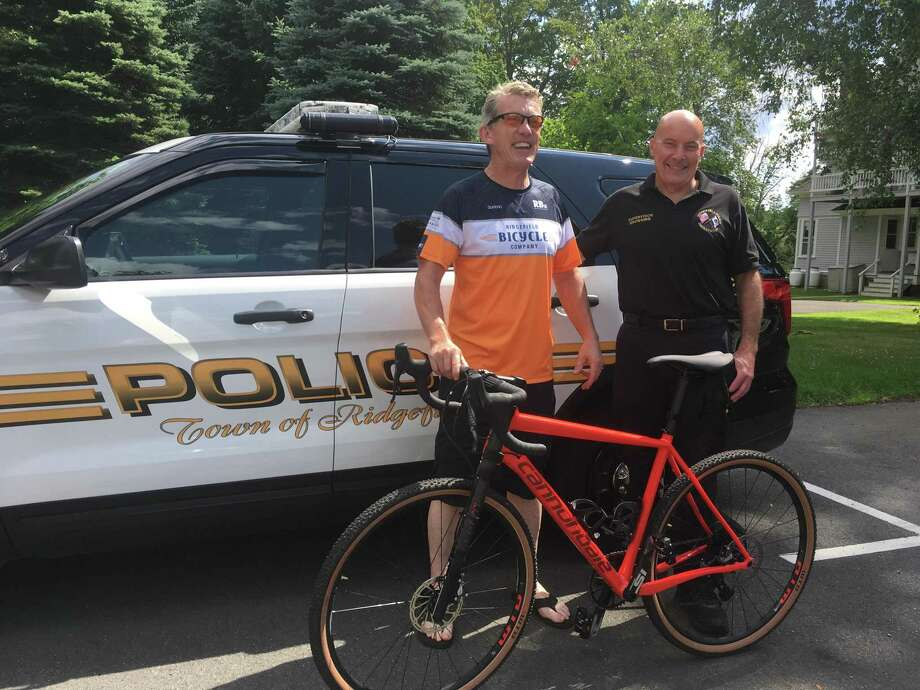 Cyclist Ciaran Carruthers (left) and police dispatcher Bill Browning (right) in front of a Ridgefield Police cruiser Wednesday, July 24. Browning is helping Carruthers raise funds for the annual Pan-Mass Challenge bicycle ride, which sees some 6,700 riders converge on Sturbridge Mass. to raise money for the Dana-Farber Cancer Institute. Photo: Peter Yankowski / Hearst Connecticut Media