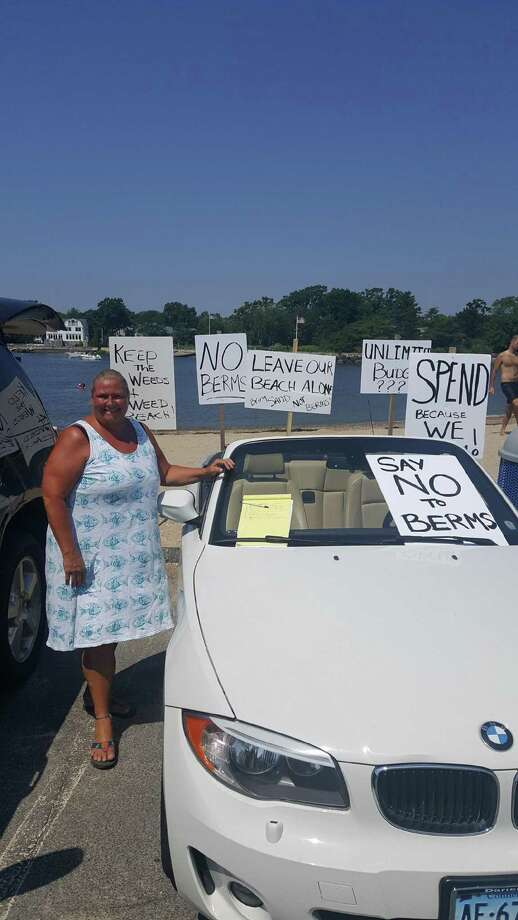 Darien resident Kelli Cole is protesting the proposed changes and improvements of Pear Tree Point Beach. She brought signs to the beach last weekend and a petition. Photo: Contributed Photo