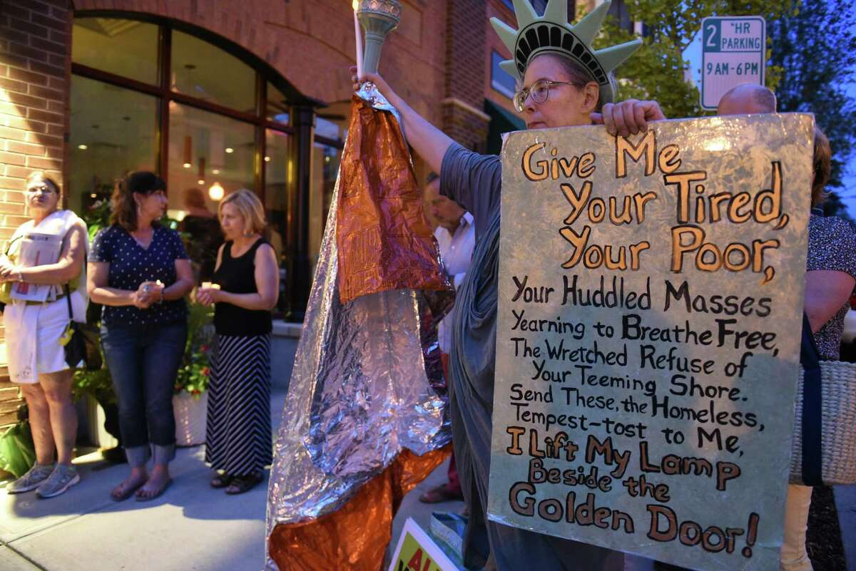 Sharon Alley of Colonie is dressed as the Statue of Liberty as the Saratoga Immigration Coalition holds a vigil to honor immigrant families worldwide outside Caffe Lena on Tuesday, July 31, 2019 in Saratoga Springs, N.Y. The vigil followed Immigrant Stories: In Their Own Words series held inside Caffe Lena. (Lori Van Buren/Times Union)