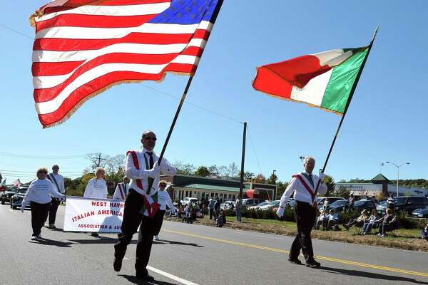 Marchers carry the American flag and Italian flag during the Greater New Haven Columbus Day Parade on Dixwell Avenue in Hamden.
