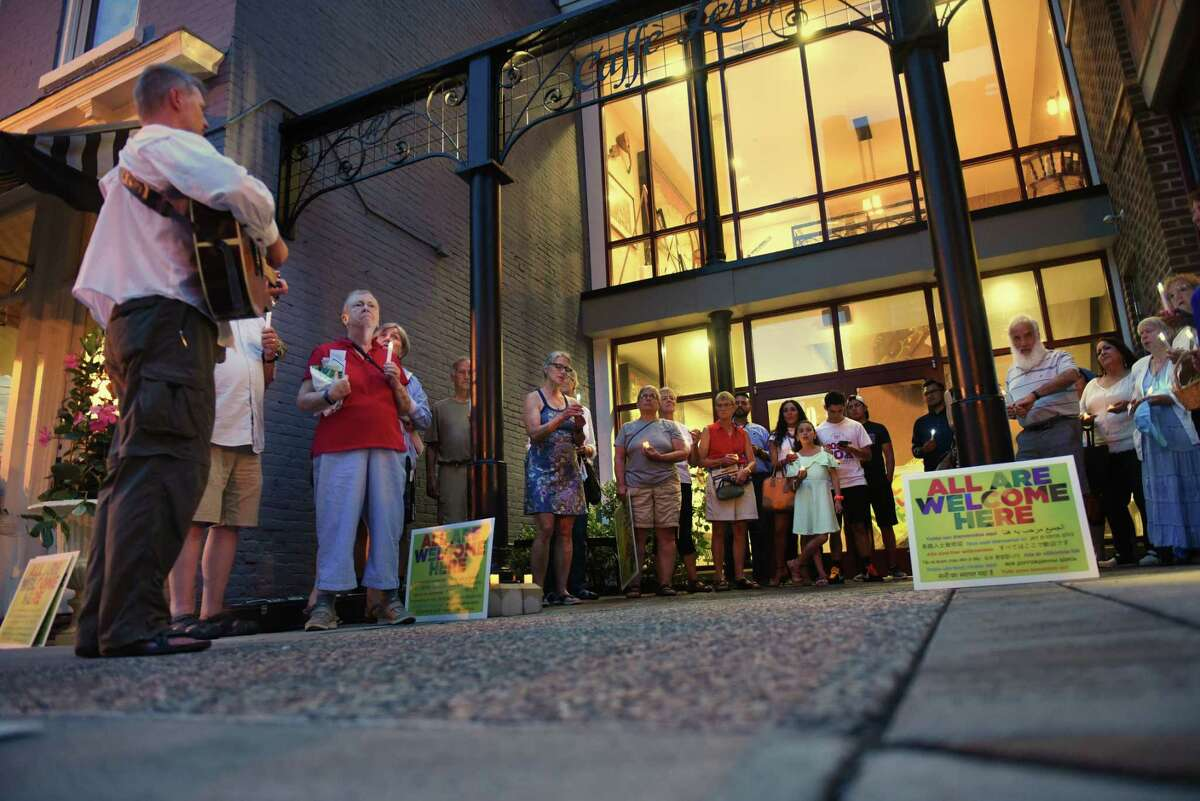 Rev. Joe Cleveland of the Unitarian Universalist Church, left, plays his guitar and leads singing as the Saratoga Immigration Coalition holds a vigil to honor immigrant families worldwide outside Caffe Lena on Tuesday, July 31, 2019 in Saratoga Springs, N.Y. The vigil followed Immigrant Stories: In Their Own Words series held inside Caffe Lena. (Lori Van Buren/Times Union)