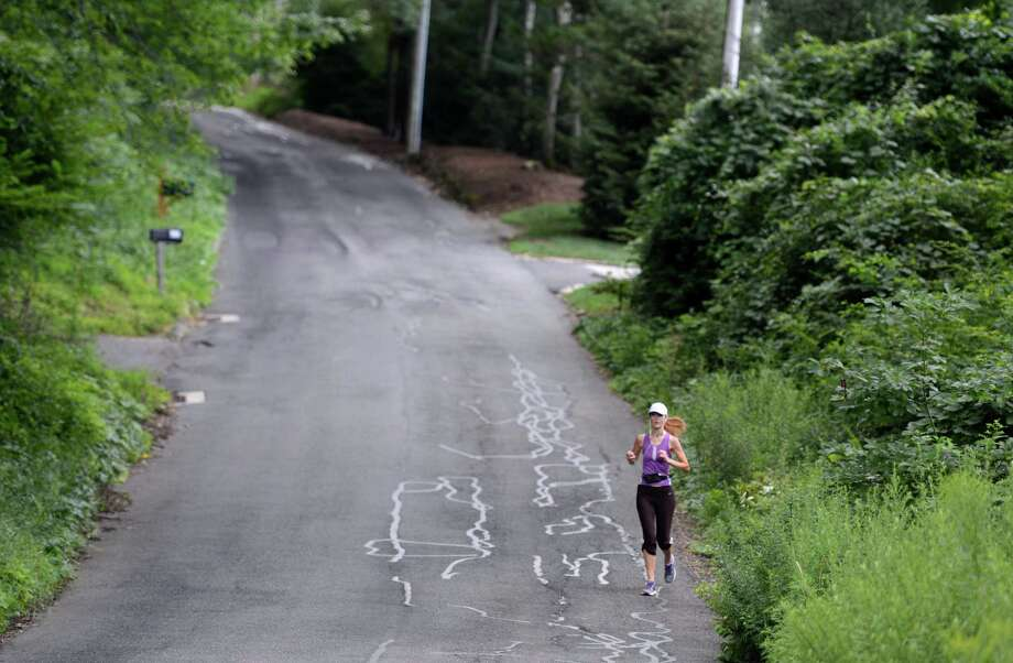 A runner comes down a hill on Topstone Road in Redding Wednesday, Aug. 5, 2015, part of the town's 19 miles of designated scenic roads. Photo: Autumn Driscoll / Hearst Connecticut Media / Connecticut Post