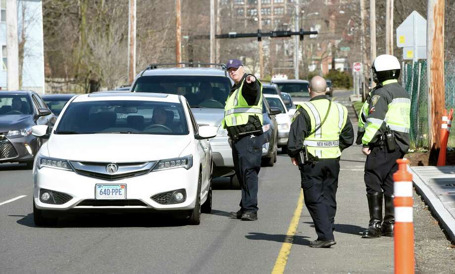 (Arnold Gold-New Haven Register) New Haven Police Officer Scott Durkin (center) directs a car to be ticketed for distracted driving on North Frontage Rd. in New Haven on 4/12/2016.