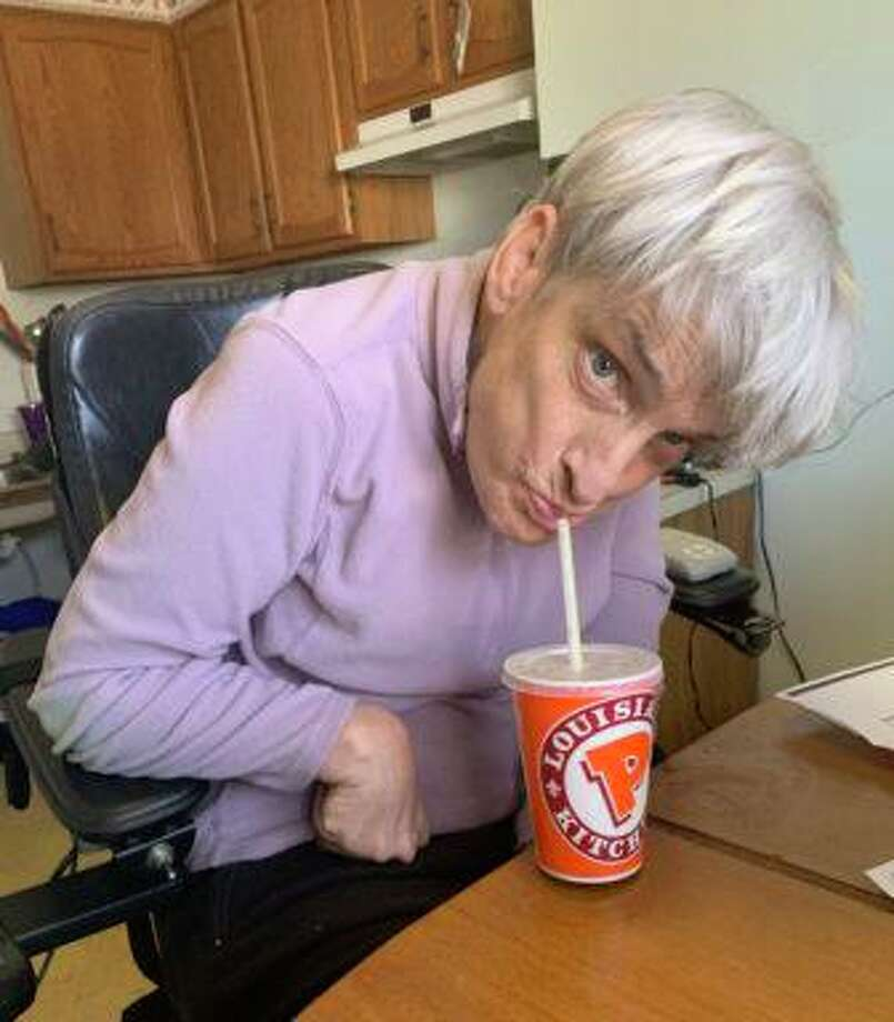 Mary Ann Langton, of West Hartford, demonstrates how a plastic straw enables her to drink independently. Photo: Jenna Carlesso / CTMirror.org