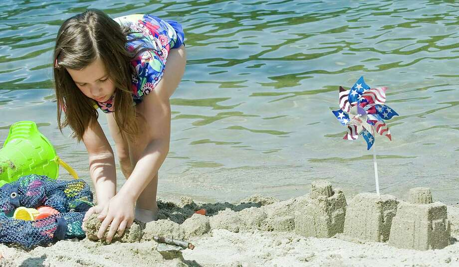 Alyssa Bello, 9 of Ridgefield, extends the wall to her patriotic castle at Martin Park Beach in Ridgefield for the Ridgefield Parks and Rec annual sand castle competition. Monday, July 4, 2016 Photo: Scott Mullin / For The / The News-Times Freelance