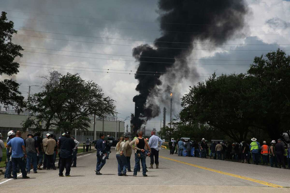 Evacuated ExxonMobilworkers take a break or watch the fire from the Baytown Olefins Plant entrance on Wednesday , July 31, in Baytown.
