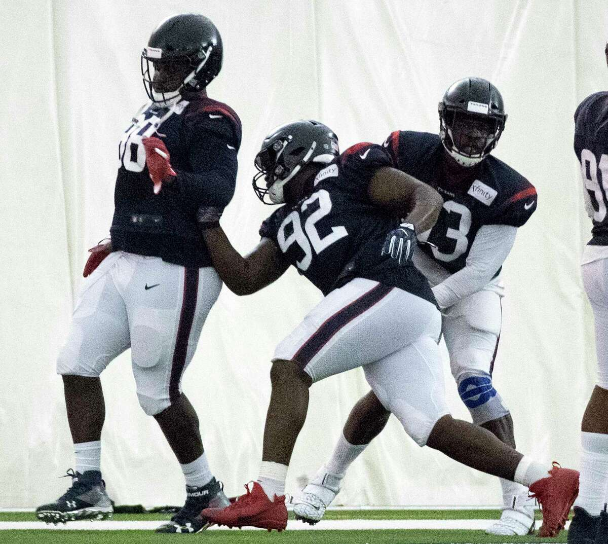 Houston Texans nose tackle Brandon Dunn (92) runs a drill against defensive ends D.J. Reader (98) and Joel Heath (93) during training camp at the Methodist Training Center on Wednesday, July 31, 2019, in Houston.