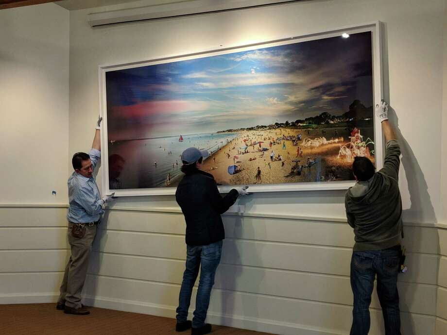 "Hanging the ""Jennings Beach, Fairfield, Day to Night,"" photograph at the Museum. Photo: Contributed Photo"