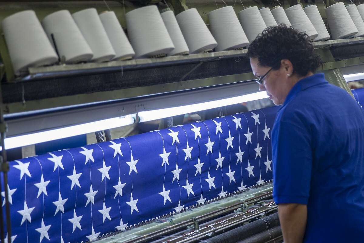Jilhy Flores checks on the machine that makes the canton of the American flag at Goodwill South Florida in Miami, Tuesday, July 2, 2019. (Charlie Ortega Guifarro/Miami Herald via AP)