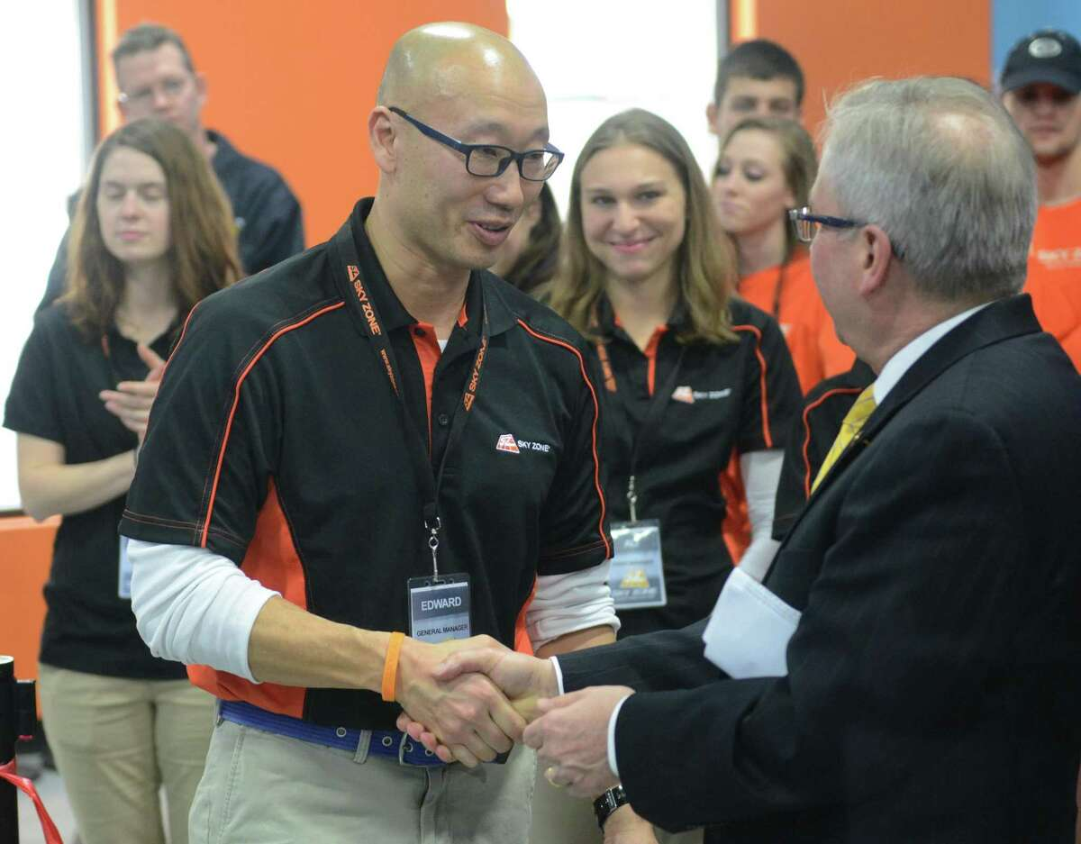 Sky Zone Owner and General Manager Edward Kim shakes hands with Bethel First Selectman Matt Knickerbocker during the grand opening of Sky Zone Indoor Trampoline Park in Bethel, Conn. Thursday, Feb. 20, 2014. Sky Zone contains several large trampoline courts including ones with a foam pit for learning tricks and basketball hoops for slam dunking. The facility also offers SkyRobics fitness classes, 3D dodgeball tournaments and the SkyRiser bungee trampoline.
