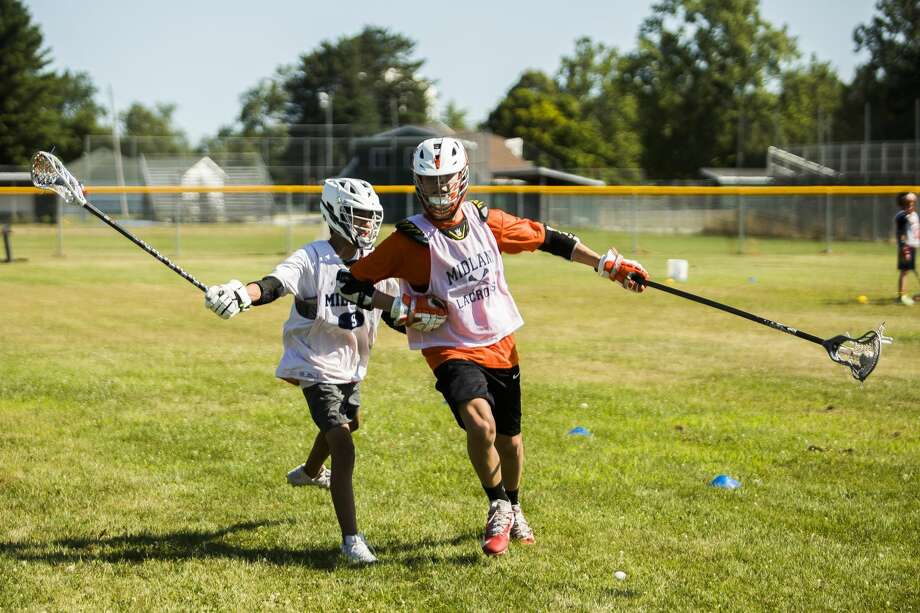 Midland residents Alvin Lopez, 16, left, and Al Pavlock, 16, right, participate in a drill during a one-day lacrosse camp with coaches from the University of Michigan lacrosse team on Wednesday, July 31, 2019 near Northeast Middle School in Midland. (Katy Kildee/kkildee@mdn.net) Photo: (Katy Kildee/kkildee@mdn.net)