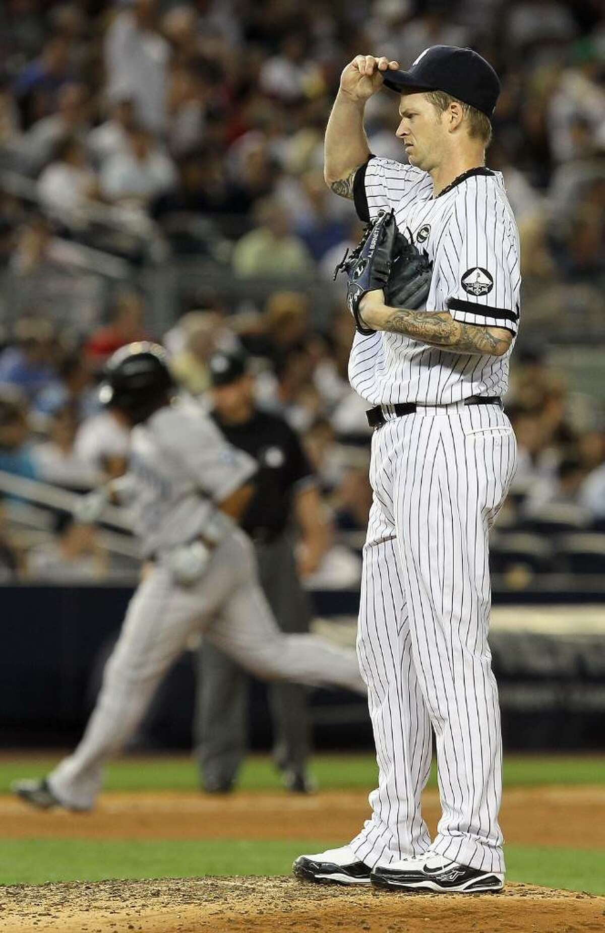 NEW YORK - AUGUST 02: A.J. Burnett #34 of the New York Yankees reacts during the fifth inning after surrendering a two run home run to Edwin Encarnacion #12 of the Toronto Blue Jays on August 2, 2010 at Yankee Stadium in the Bronx borough of New York City. (Photo by Jim McIsaac/Getty Images) *** Local Caption *** A.J. Burnett;Edwin Encarnacion