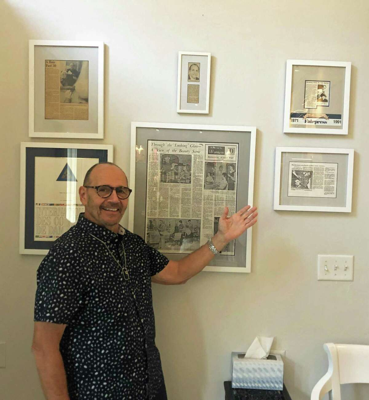 Charles Tuozzoli points to framed articles about his 1974 lawsuit, where he won the right to cut both men's and women's hair.