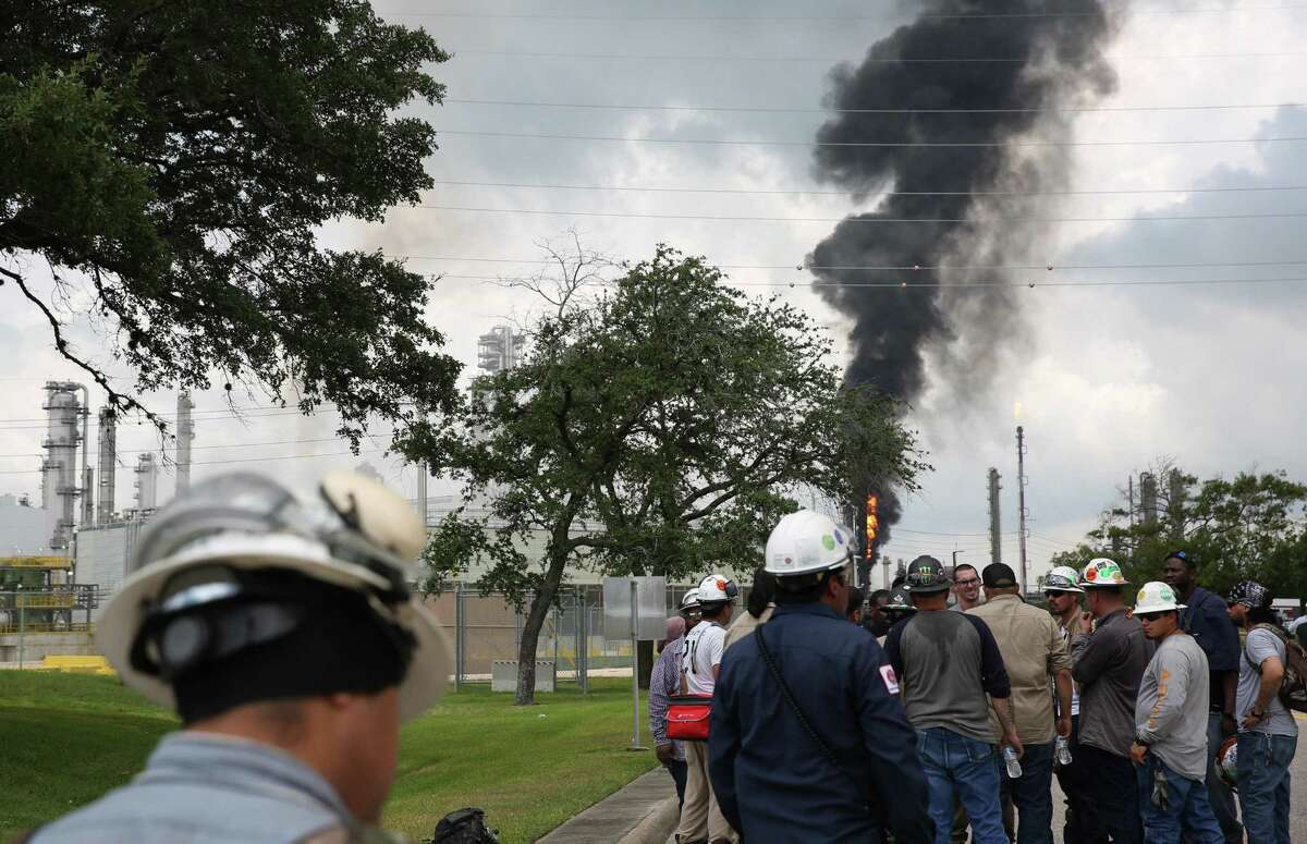 Evacuated ExxonMobil workers take a break or watch the fire from the Baytown Olefins Plant entrance on Wednesday , July 31, in Baytown.