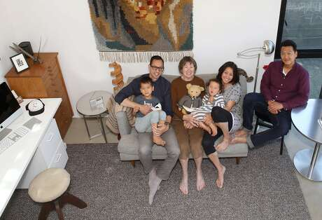 View of the living room at �Kleines Haus,� a simple, sleek tiny home designed by Peter Liang (left) carrying his nephew Otto, his mother, Irmhild Liang (middle), Stephanie Liang Chung (right) carrying her daughter Liezl, and her husband Mike Chung (right) seen on Thursday, July 18, 2019 in Oakland, Calif.