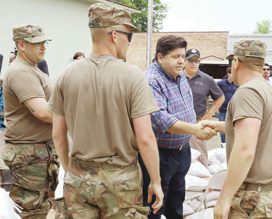 Gov. J.B. Pritzker, center, greets members of the Illinois National Guard on June 4 during a stop in Grafton to get a first hand look at flooding in the small town. The guardsmen had been helping to fill sandbags.