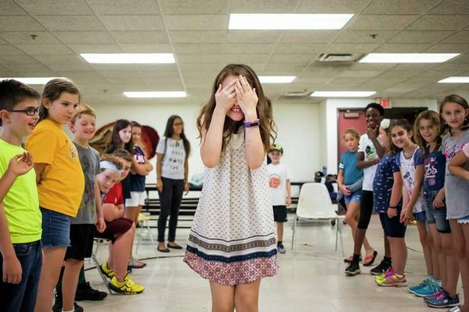 Lorelai Boldt covers her eyes while walking between two lines of classmates during the second session of a weeklong improv camp on Tuesday at Midland Center for the Arts. For more photos, go to www.ourmidland.com. (Katy Kildee/kkildee@mdn.net)