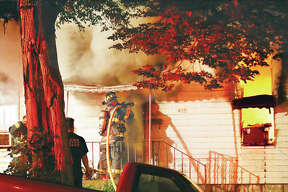 An Alton firefighter directs a hose line through the front door of a house early Wednesday morning in the 400 block of Monument Avenue as flames burn inside the house as seen through the window, right. A body was eventually found inside the house in a room believed to be the living room. East Alton firefighters assisted with the blaze. Fire officials were unsure of the victim's identity Wednesday afternoon.