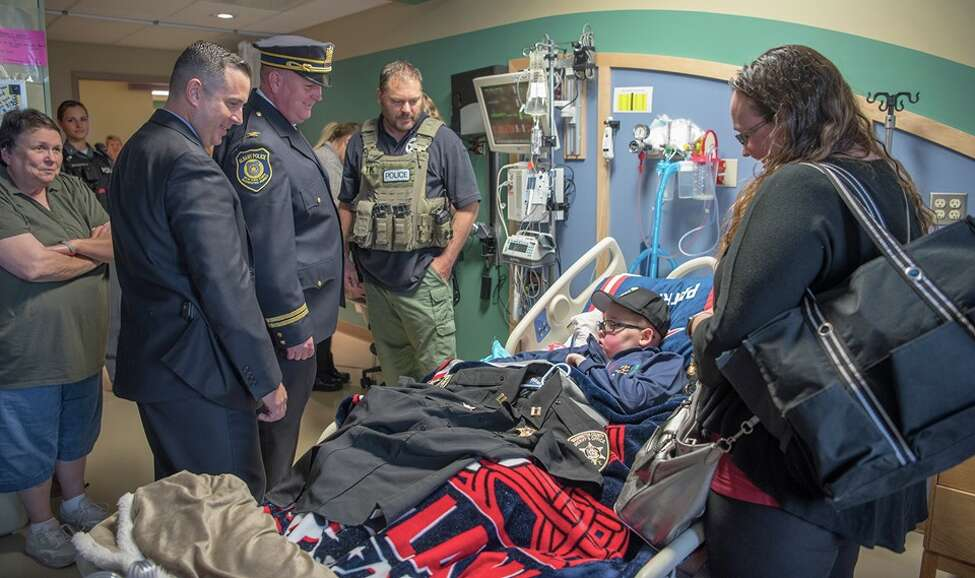 Officers from local, state and federal law enforcement agencies line the halls of Albany Medical Center on Wednesday to show their support for John Hoague-Rivette, an 11-year-old boy with brain cancer who was discharged and being taken home for hospice care.