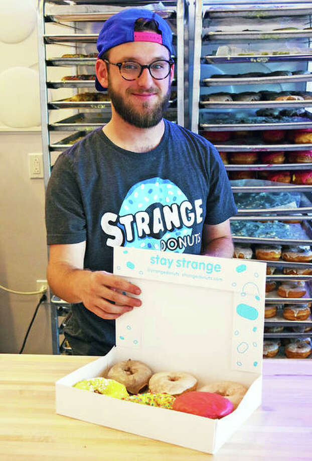 Holden Martinez, store manager for the new Strange Donuts store in Edwardsville, shows off a small sample of flavors the store has to offer. Based in Creve Coeur, Missouri, the company initially is planning three locations in the Metro East. Photo: Tyler Pletsch | Hearst Illinois