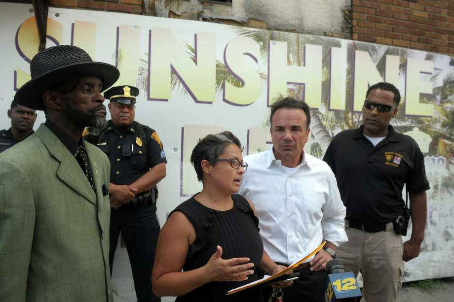 Bridgeport health director Maritza Bond, center, speaks at a news conference outside Sunshine Deli, on Stratford Avenue., in Bridgeport on Wednesday. She was accompanied by City Council Ernie Newton and Mayor Joe Ganim. Photo: Ned Gerard / Hearst Connecticut Media / Connecticut Post