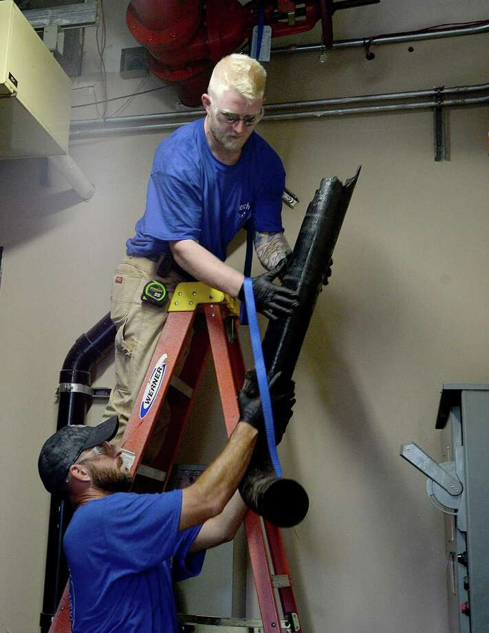 Apprentice James Richardson hands off a cracked and leaking section of piping to his boss Shuan VonFeldt, a responsible master plumber and president of Benchmark Plumbing, make repairs at the Beaumont Tower building. VonFeldt pursued a career in the plumbing trade after becoming disenchanted with the opportunities available using his associate's degree in computer networking. After 10,000 hours working as an apprentice and passing the test to be licensed as a master plumber, VonFeldt says he is now earning far more than he would have in his original career path. He now encourages high school students to consider pursuing work in skilled trades like plumbing.  Tuesday, August 7, 2018  Kim Brent/The Enterprise Photo: Kim Brent / The Enterprise / BEN