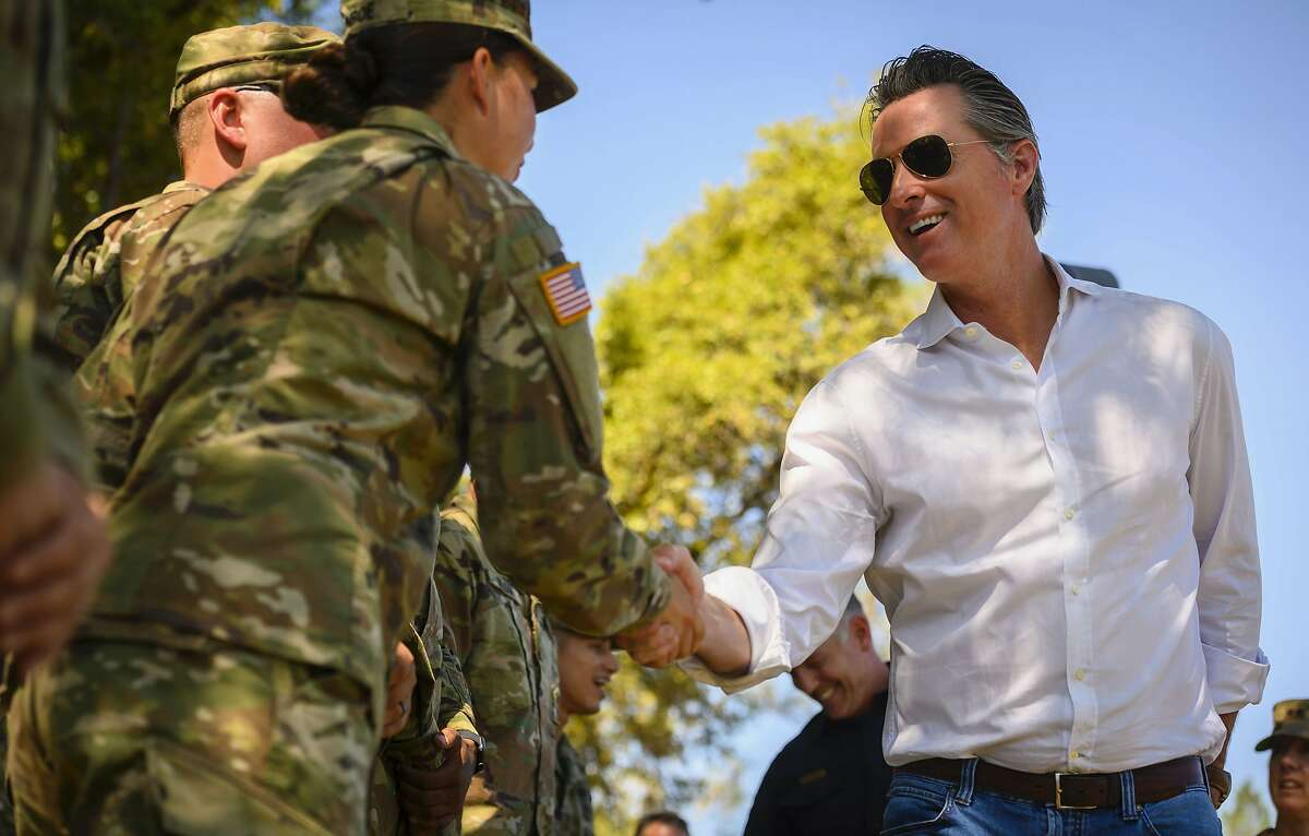 Gov. Gavin Newsom shakes hands with a member of the National Guard on Wagon Trail in the Sierra Foothills in Colfax, Calif. Wednesday, July 31, 2019. (Daniel Kim/The Sacramento Bee via AP, Pool)