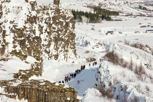 Thingvellir National Park covered in fresh snow in Iceland during winter. Almannagja gorge with visitors. Thingvellir is part of UNESCO world heritage. Northern Europe. Scandinavia. Iceland. February. (Photo by: Martin Zwick/REDA&CO/Universal Images Group via Getty Images)