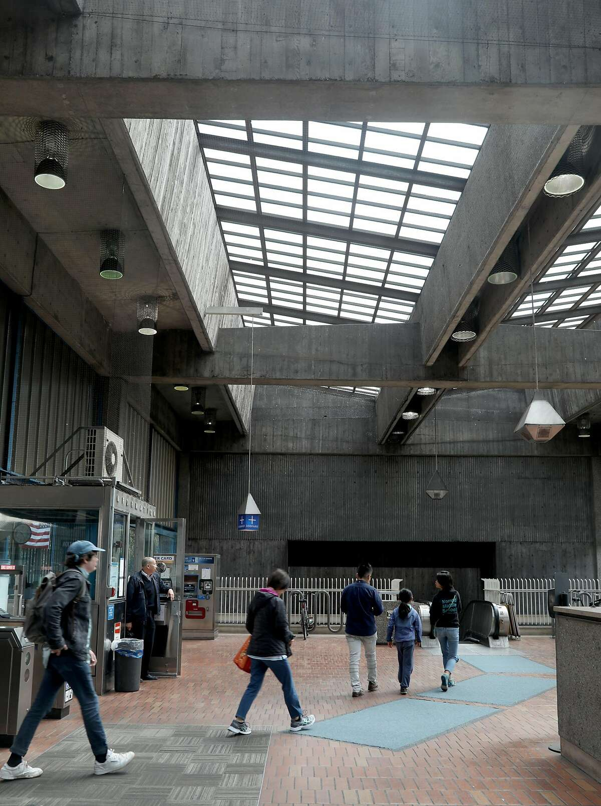 Commuters enter the Glen Park BART station. It was designed by a noted architect, Ernest Born, and follows the precepts of Brutalism, but does it deserve its recent nomination for the National Register of Historic Places?