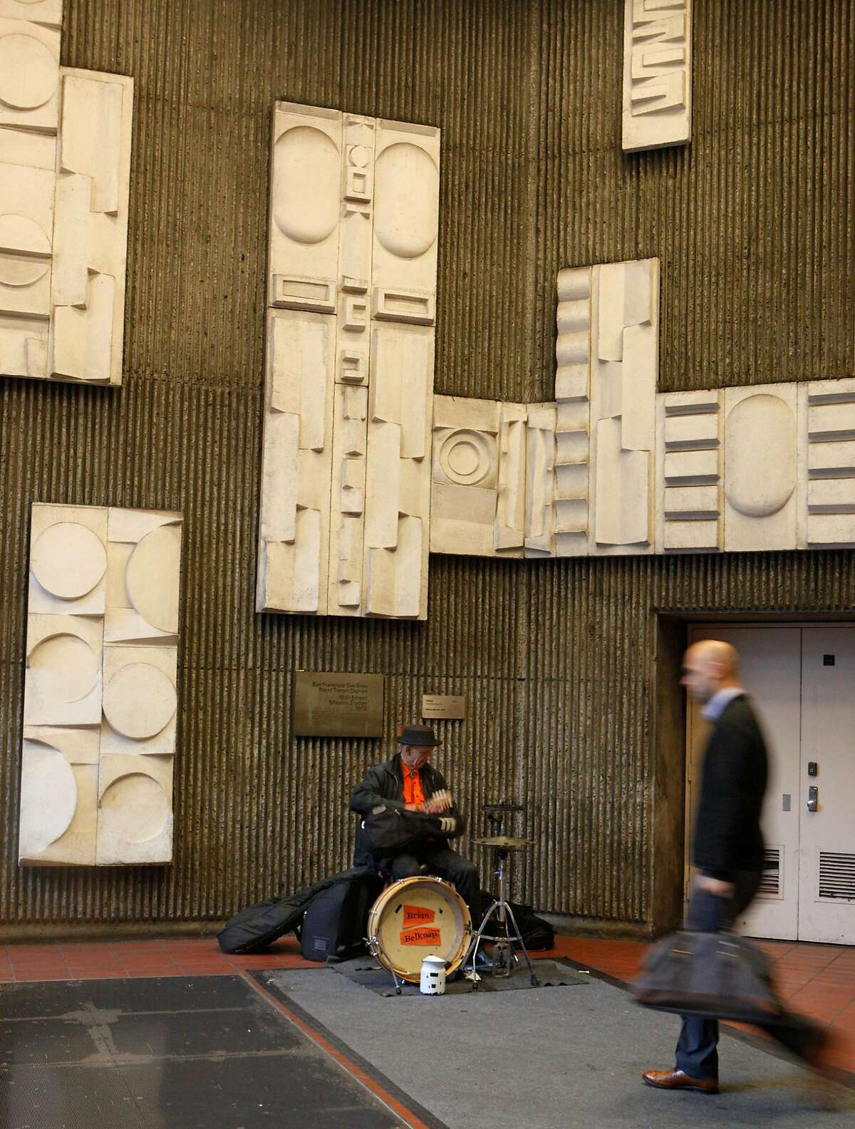 William Mitchell's concrete relief of matte white tiles at the 16th Street BART station, shown here behind musician Brian Belknap in 2015, are an underrated part of the experience at this station.