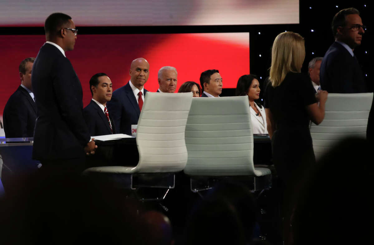 Democratic presidential candidates former housing secretary Julian Castro (3rd L) (L-R) Sen. Cory Booker (D-NJ), former Vice President Joe Biden, Sen. Kamala Harris (D-CA) (partially seen), former tech executive Andrew Yang, and Rep. Tulsi Gabbard (D-HI) take the stage at the Democratic Presidential Debate at the Fox Theatre July 31, 2019 in Detroit, Michigan. 20 Democratic presidential candidates were split into two groups of 10 to take part in the debate sponsored by CNN held over two nights at Detroit's Fox Theatre.