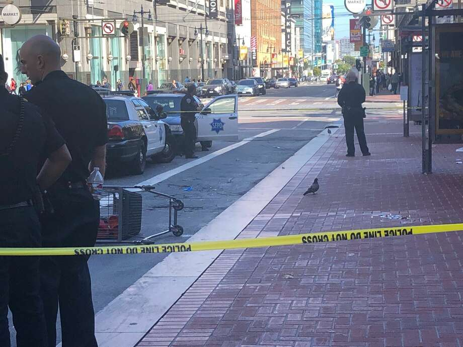 San Francisco police officers gathered on the scene at the intersection of Market St. and Fifth St. Witnesses report a dog was shot. Photo: Nikki Tran / SFGate