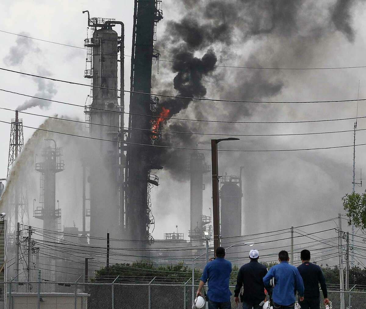 Workers watch a fire burn at the ExxonMobil Baytown Olefins Plant on Wednesday, July 31, 2019, in Baytown.