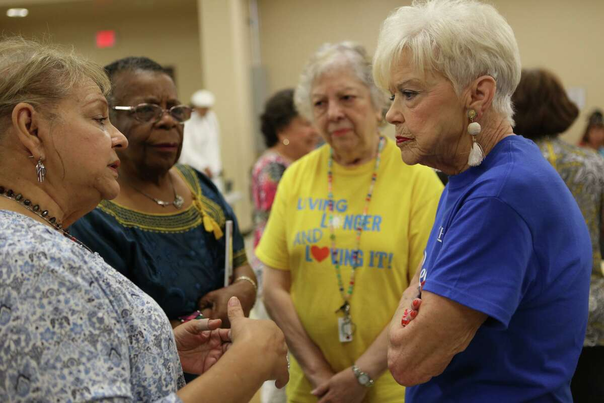 """Doris Griffin (in blue) listens to Cynthia Martinez ask questions July 25 after the presentation at Doris Griffin Senior Center, located on San Antonio's Northwest Side. Griffin encouraged questions from the audience and explained the importance of the senior community. """"I want to encourage you to get involved,"""" Griffin said."""